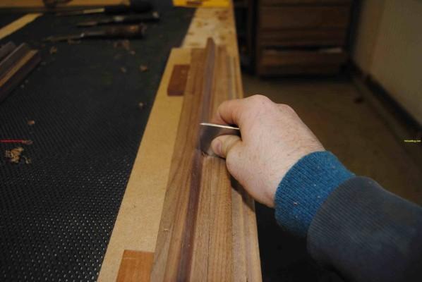 Using custom made scraper to shape the sideboard door handles